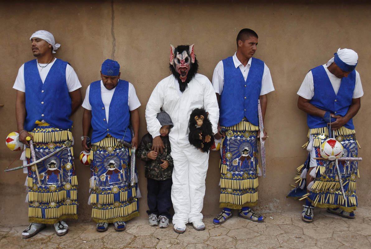 Members of La Danza del Santo Nino take cover from the rain against the side of El Santuario de Chimayo in Chimayo, New Mexico April 24, 2011. Thousands of people walk to the little chapel over Easter weekend where they believe the dirt inside holds the power to heal, some from as far away as Mexico and Colorado.