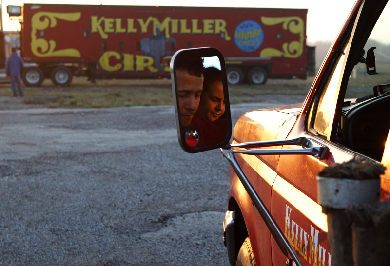 Performer Adilson Fernandes and his wife Iragilda are reflected in the rear view mirror of their truck as they arrive on the lot at sunrise, where the Kelly Miller Circus will be set up for the day, in Crandall, Texas March 18, 2009. The Kelly Miller Circus, which was founded in 1938 and is based in Hugo, Oklahoma, travels to over 220 cities and towns each year throughout the United States.