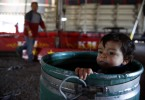 Edward Samuel Perez, 15 months old, plays in a barrel as his father sets up the big top at the Kelly Miller Circus in Crandall, Texas March 18, 2009.