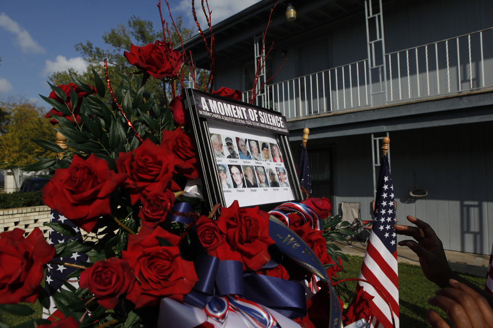 Neighbors place a photo of the victims of the shootings at Fort Hood on top of a wreath of flowers set up as a memorial in the courtyard of the apartment complex where suspected shooter, Major Nidal Malik Hasan, lived in Killeen, Texas November 9, 2009. Thirteen people died in the mass shooting Thursday at the sprawling U.S. Army base in Texas.