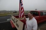 Mark Rodgers holds an American flag and stands beside a sign on the back of his pick-up truck that reads,