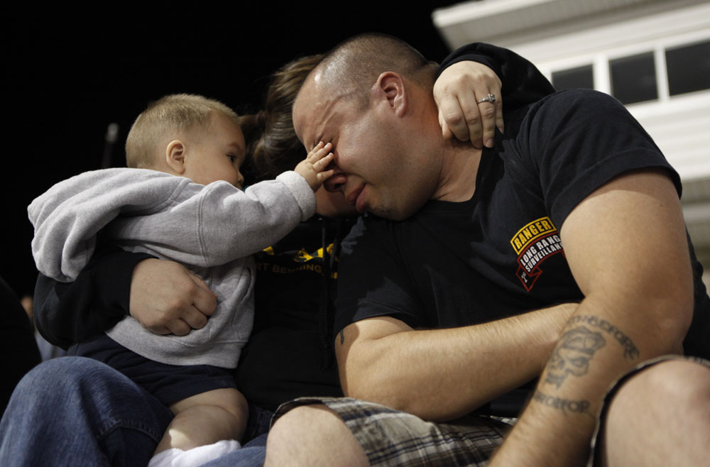 Owen Rabago, (L), wipes a tear away from his father, Specialist Sheldon Rabago's face, (R), as his mother Nancy wraps her arms around both of them during a candle light vigil at Hood Stadium on the Fort Hood Army Post in Fort Hood, Texas November 6, 2009. The death toll from an Army psychiatrist who opened fire at the Fort Hood Army post rose to 13 on Friday, and Army officials said the suspected shooter was hospitalized and on a ventilator.