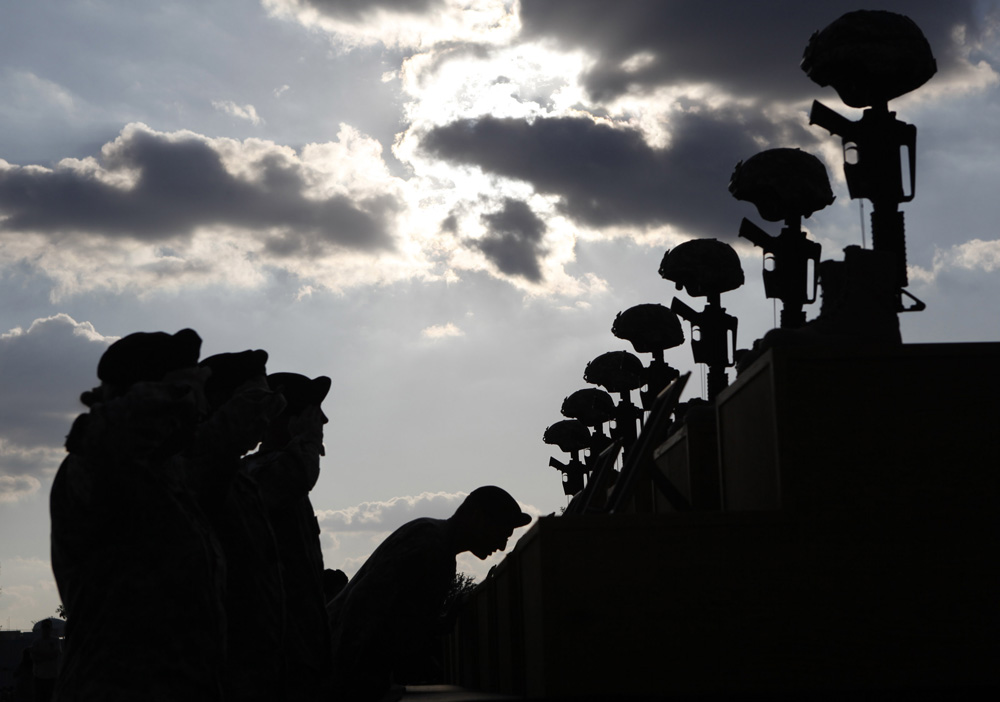 U.S. soldiers pay their respects in front of fallen soldier memorials for the shooting victims after the III Corps and Fort Hood Memorial Ceremony at Fort Hood, Texas, November 10, 2009. The memorial was held to honor the 13 victims of the shootings which took place on the Fort Hood Army post on November 5.