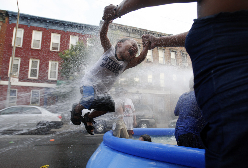 A woman swings a child through the spray from a fire hydrant during a heat wave in the Bushwick section of Brooklyn, New York July 6, 2010.