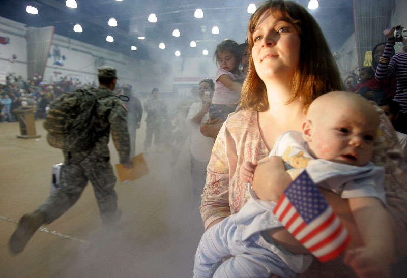 A woman watches as soldiers from the Army 4th Infantry Division arrive at a homecoming ceremony in Fort Hood, Texas November 28, 2006. The division returned after spending a one year tour of duty in Iraq.