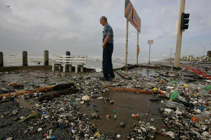 A man looks over the edge of the sea wall as Hurricane Ike approaches in Galveston, Texas September 12, 2008.