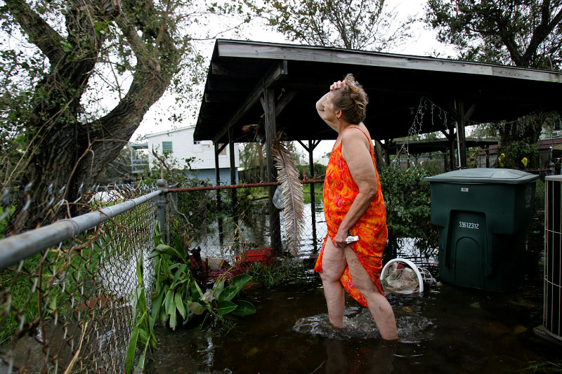 Gail Meads looks for her cat which climbed up into a tree as she stands in her backyard ankle deep in floodwaters caused by Hurricane Ike in Galveston, Texas September 13, 2008.