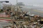 A man walks amid debris from Hurricane Ike that was cleared from the road in Galveston, Texas September 13, 2008.