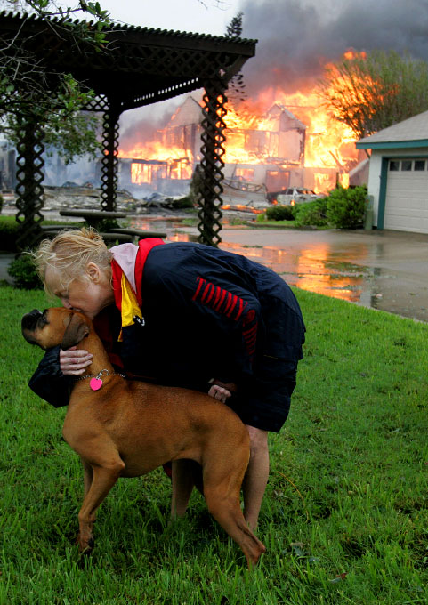 Frederika Kotin kisses her dog Belle as her home burns behind her after Hurricane Ike hit Galveston, Texas September 13, 2008.