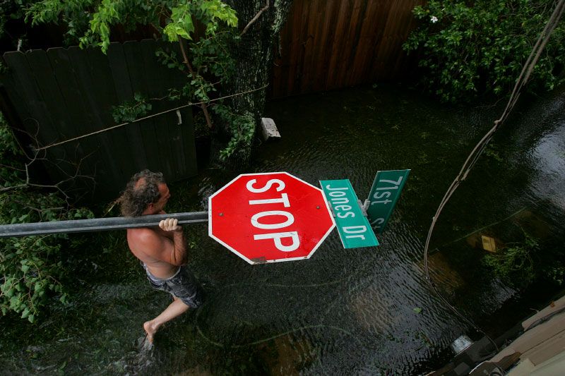 Kim Hyatt carries a street sign after Hurricane Ike hit Galveston, Texas September 13, 2008.