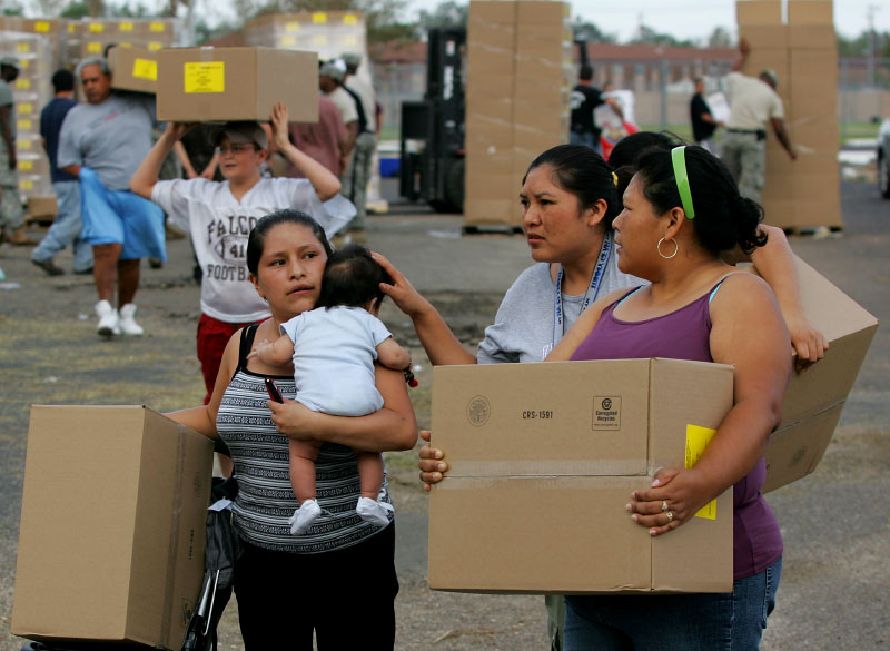 Residents carry boxes filled with Meals Ready to Eat (MRE) after picking them up from a Federal Emergency Management Agency point of distribution set up after Hurricane Ike knocked out power in Pasadena, Texas September 15, 2008.
