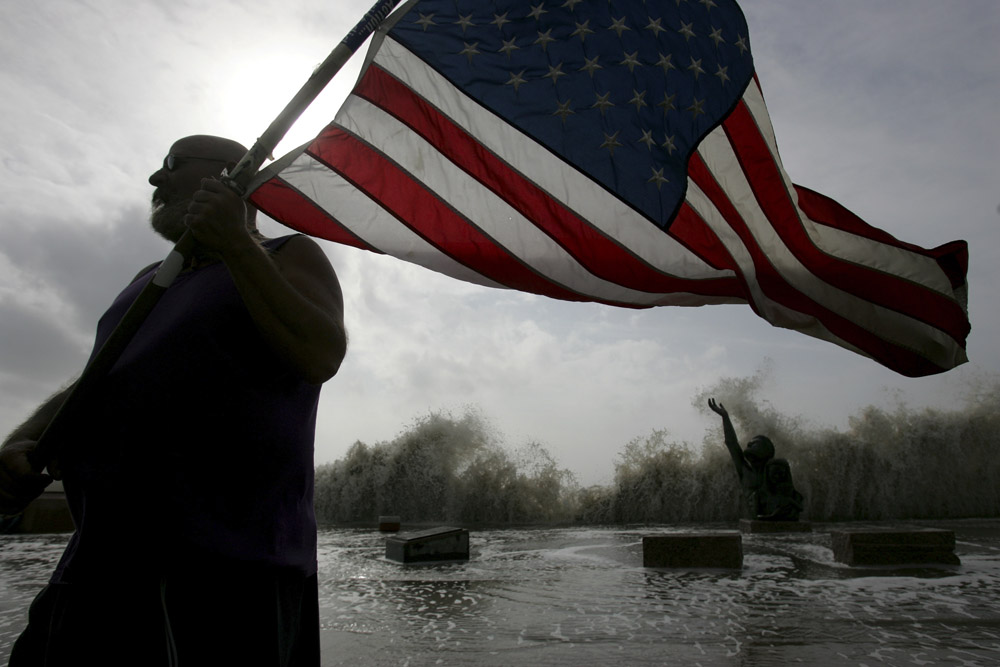 Robert Shumake holds an American flag as high swells caused by Hurricane Ike break behind him in Galveston, Texas September 12, 2008.  Hundreds of thousands of people fled coastal areas in the path of Hurricane Ike on Thursday as the storm gathered strength on a collision course with the Texas Gulf Coast, threatening to swamp populous areas around Houston under a massive wave of water.