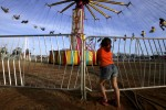 A girl watches people on a carnival ride at the annual Rattlesnake Round-up in Sweetwater Texas March 11, 2006.
