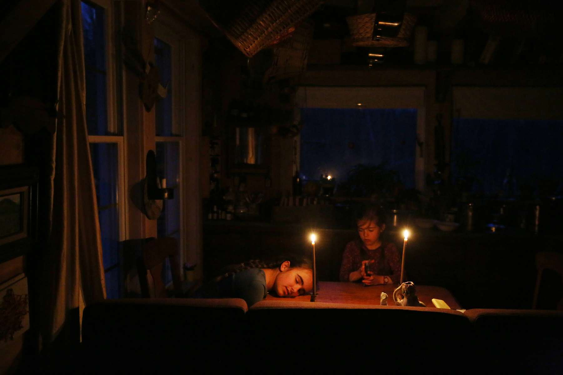 Belfast, ME, 04/29/2019 --  After a long day Etta Hughes, 11, rests her head on the kitchen table as she and her sister, Isla, 7, play a card game by candle light at their permaculture homestead in Maine. The Hughes family doesn't use electricity which is part of their petroleum-free, off-the-grid community in Maine called The Possibility Alliance.