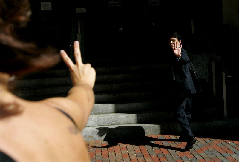 A friend flashes the victory symbol to undocumented worker Mario Rodas, 19, as he makes his way into the Federal Building for his deportation hearing in Boston, Massachusetts June 27, 2006.