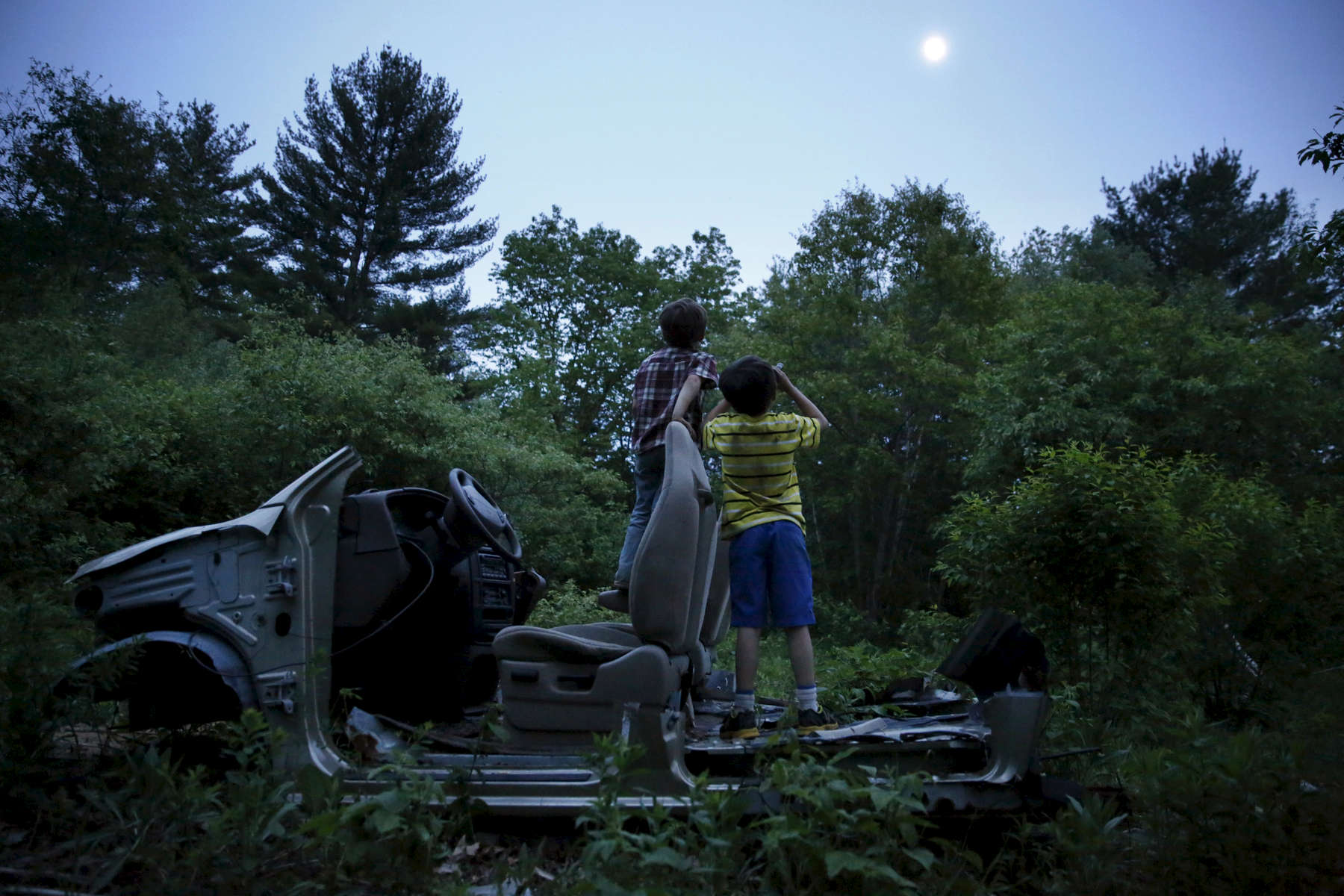 "Oxford, Maine -- 5/29/2015--  On the night of the eviction the boys climbed into a rusted Ford sunk behind the horse field. Strider held a broken automotive hose to his eyes like a pair of binoculars. He tipped his head upward. ""What's on the moon?"" Strider asked.Jessica Rinaldi/Globe Staff"