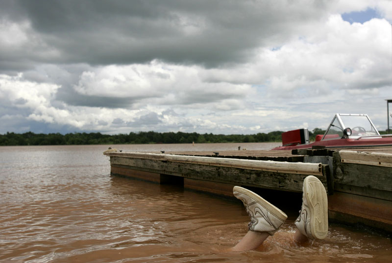 Colby Deck, 18, dives underwater while noodling for catfish in Pauls Valley, Oklahoma June 30, 2007. Noodling is the sport of fishing by hand instead of using a rod and reel.