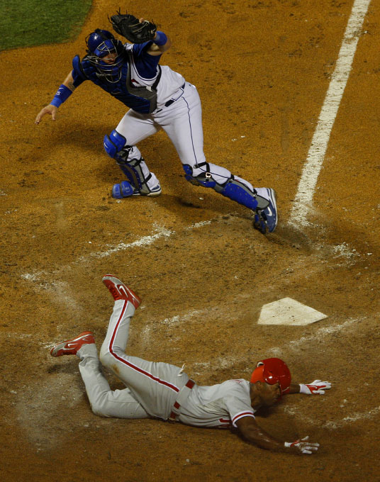 Philadelphia Phillies Jimmy Rollins loses his helmet after Texas Rangers catcher Jarrod Saltalamacchia (top) tagged him out during the sixth inning of interleague MLB baseball action in Arlington, Texas June 28, 2008.