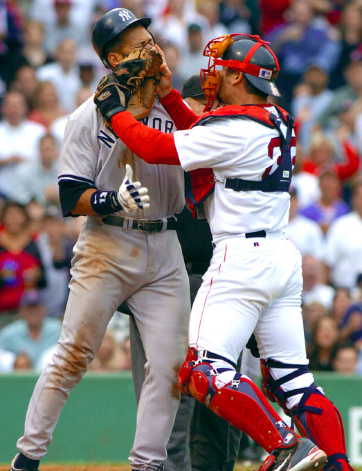 Boston Red Sox catcher Jason Varitek (R) pushes his glove into New York Yankees player Alex Rodriguez's face at Fenway Park in Boston, Massachusetts July 24, 2004.