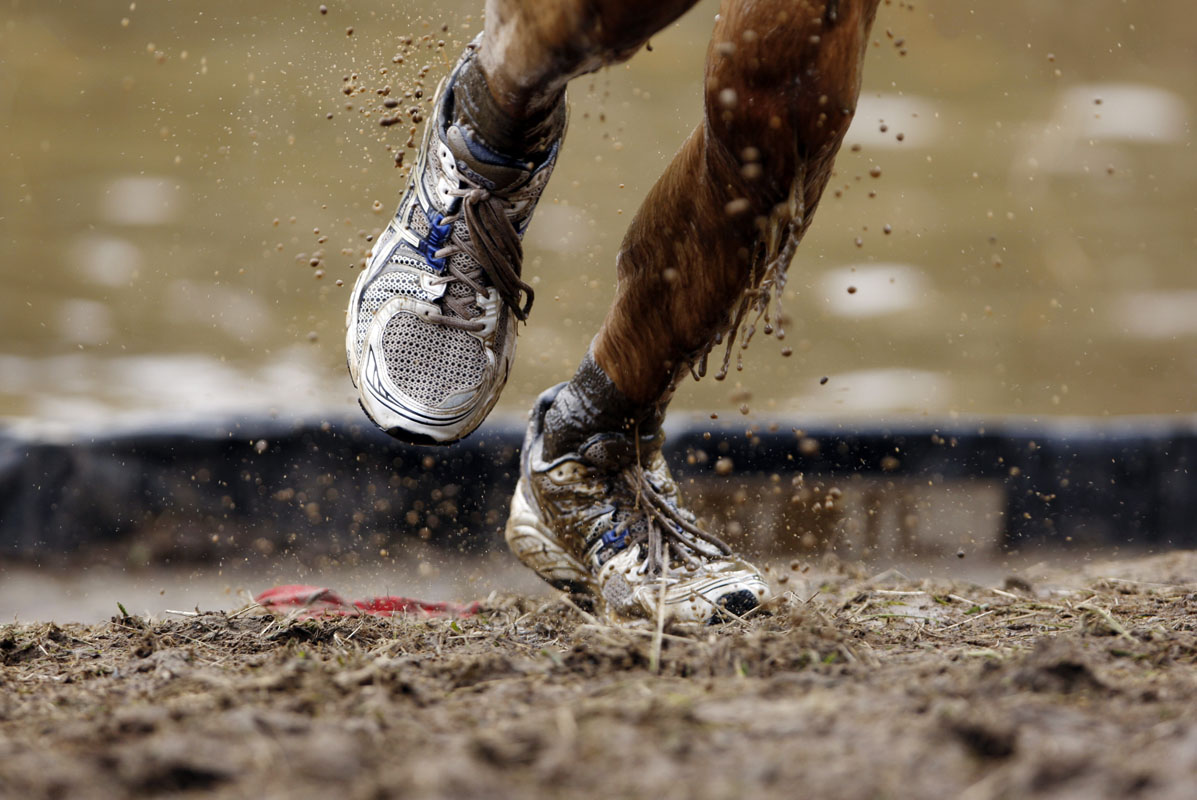Mud flys off of a competitors shoes as he runs out of an obstacle during the Tough Mudder at Mt. Snow in West Dover, Vermont July 15, 2012. The Tough Mudder is a nine mile endurance event which runs competitors through a military style obstacle course complete with mud, water and fire.