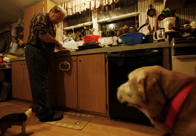Trapper and Animal Control Officer Harold Renfro cuts up the beaver he trapped earlier in the day as his dogs wait for scraps in Sacul, Texas December 6, 2008.