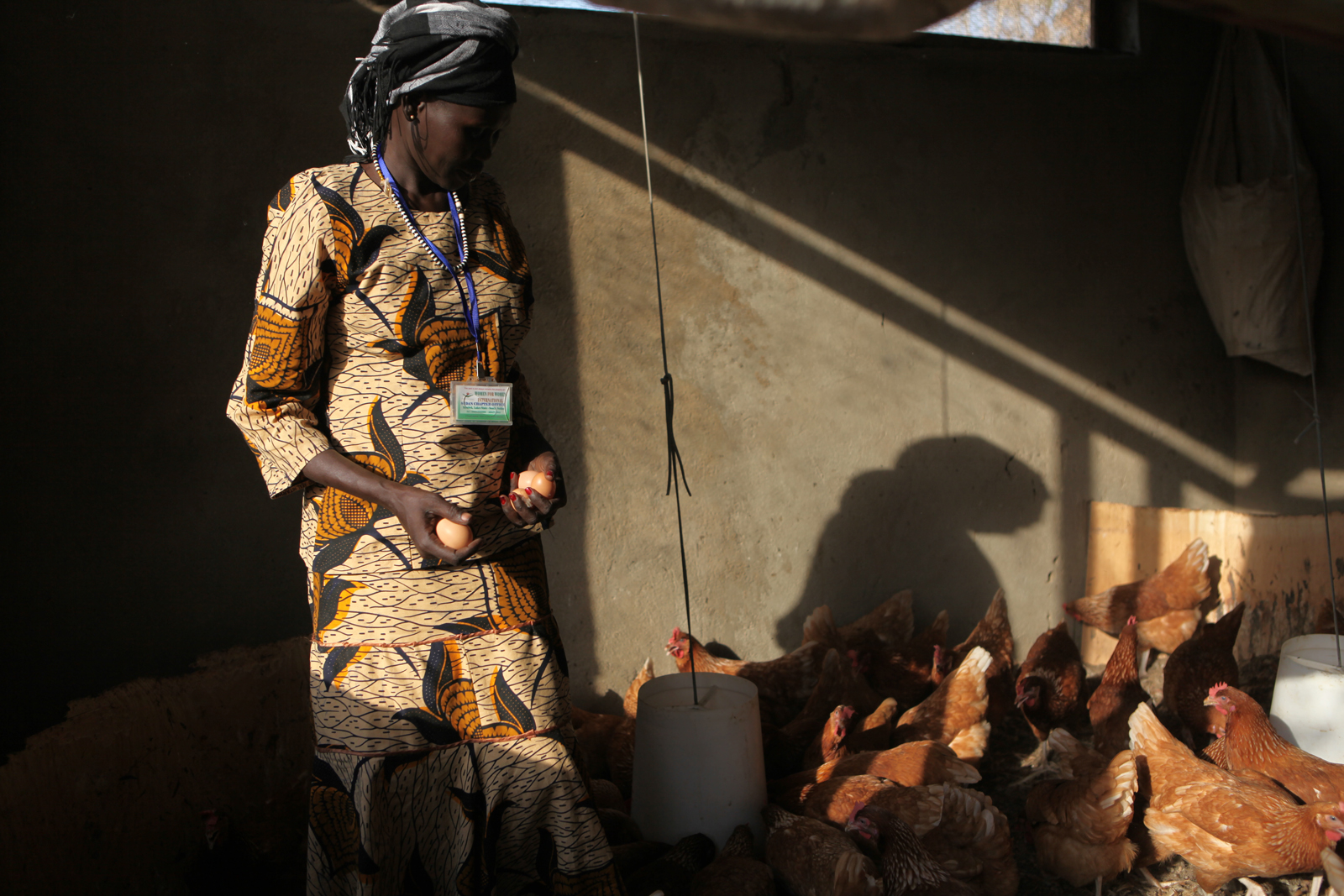 Women for Women International Sudan Chapter runs the Pacong Community Farm for women from Rumbek East, Lakes State, South Sudan. The farm supports vegetable farming, an aviary honey project, livestock and poultry. Women's Trainer Margaret Achol collects eggs from the poultry project.