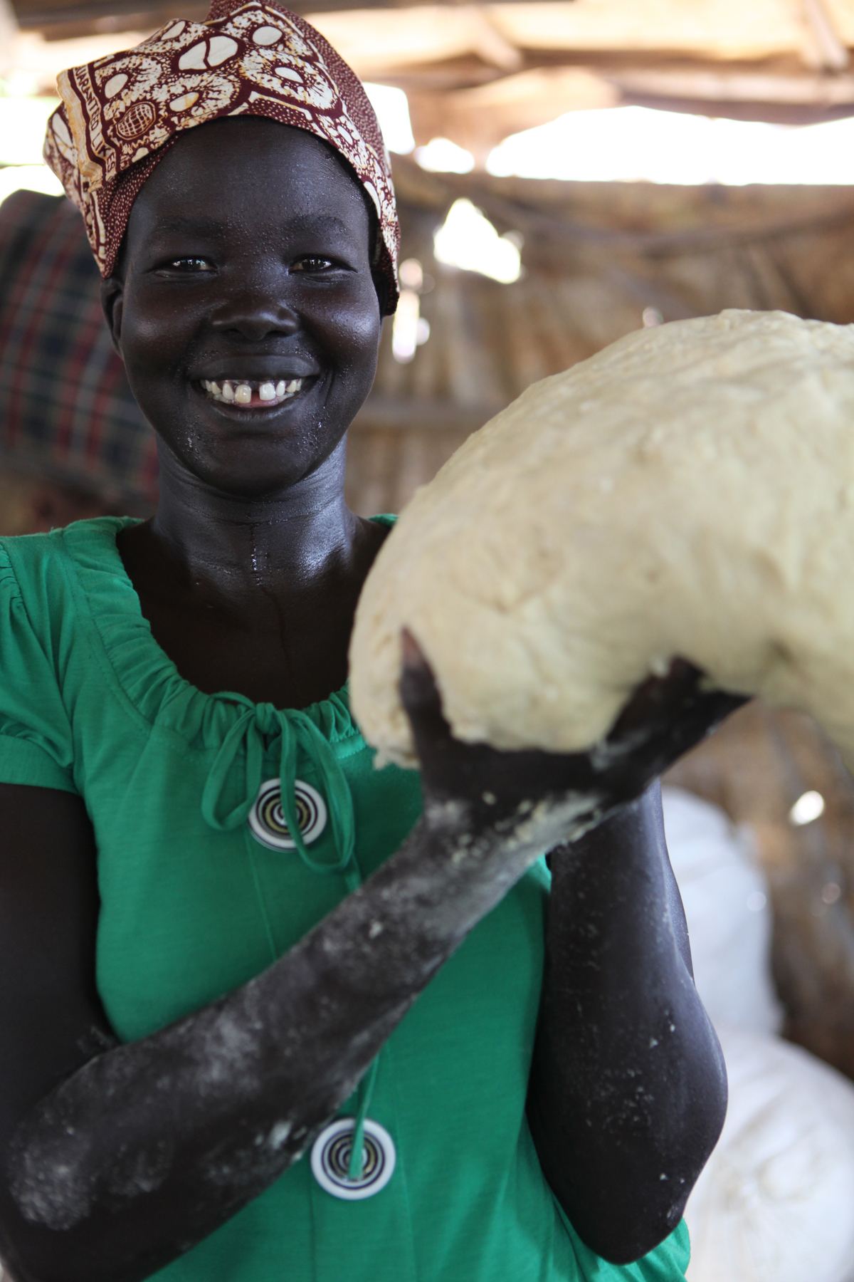 Women for Women International Sudan Chapter is opening a bakery for women from Rumbek East, Lakes State, South Sudan. While the bakery construction is completed, WfWi contracts a local baker to train the women in making donuts, rolls and bread loaves. Rebecca Chol Mabul with the dough she has made for donuts.
