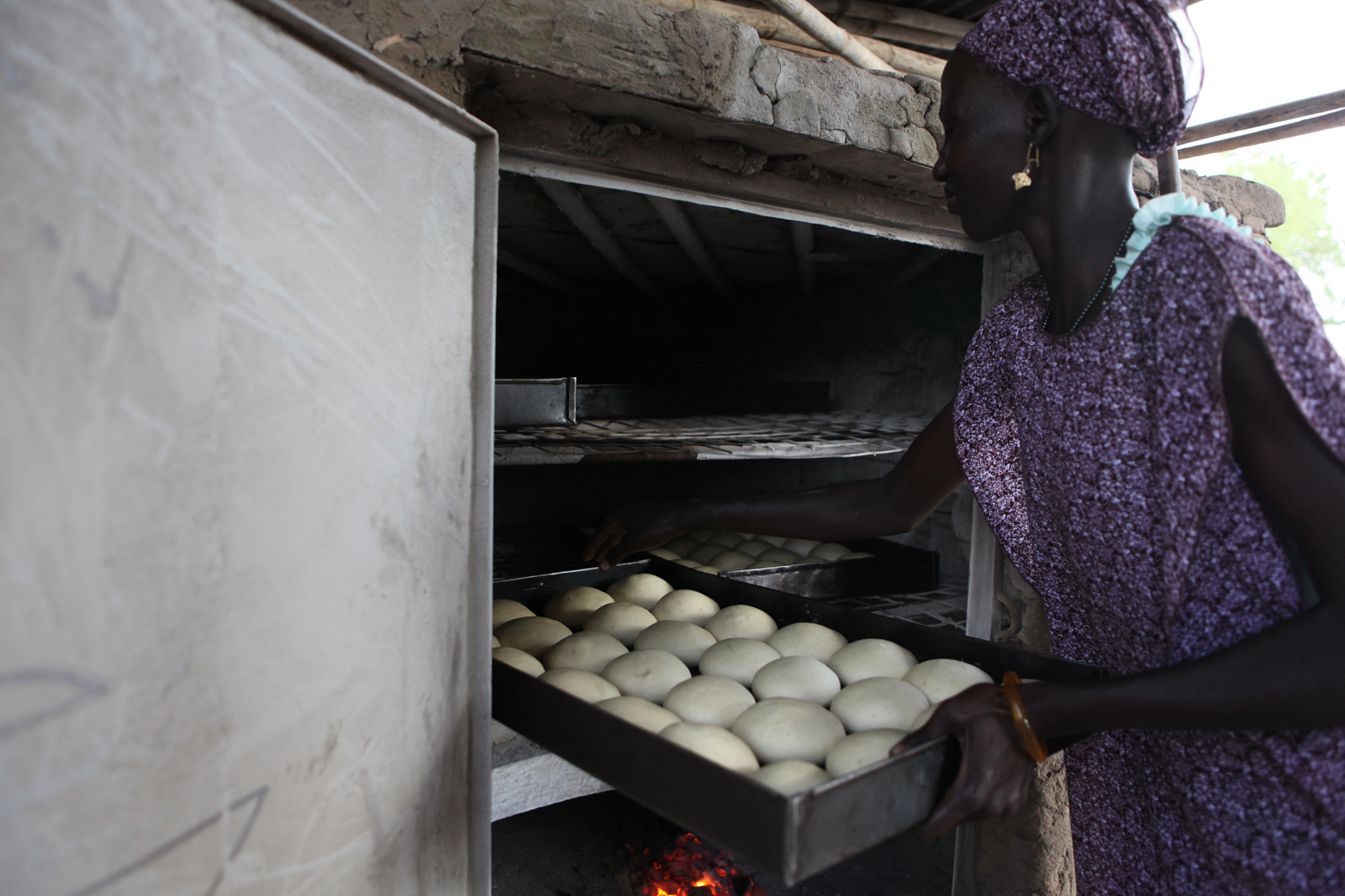 Women for Women International Sudan Chapter is opening a bakery for women from Rumbek East, Lakes State, South Sudan. While the bakery construction is completed, WfWi contracts a local baker to train the women in making donuts, rolls and bread loaves. Mary Ajak Malek puts bread loaves into the charcoal oven.