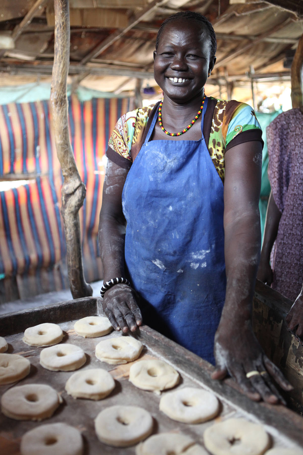 Women for Women International Sudan Chapter is opening a bakery for women from Rumbek East, Lakes State, South Sudan. While the bakery construction is completed, WfWi contracts a local baker to train the women in making donuts, rolls and bread loaves. Debora Yom learns how to cut donuts from the kneaded dough.