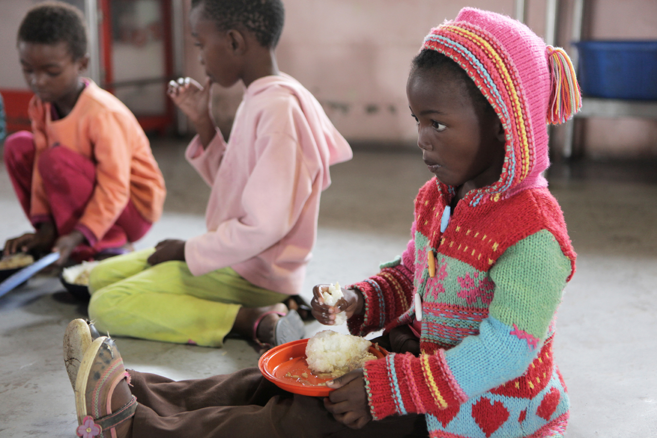 Children at the Save the Children Sizolomphakathi Drop-in Centre in Mpumalanga Province sit to eat a hot meal. Many children in the area live in single-parent households, either due to separated parents, a deceased parent or an absent father. In early 2010, Save the Children recognised the need to open a drop-in centre for children in the area, which now serves over 133 children.