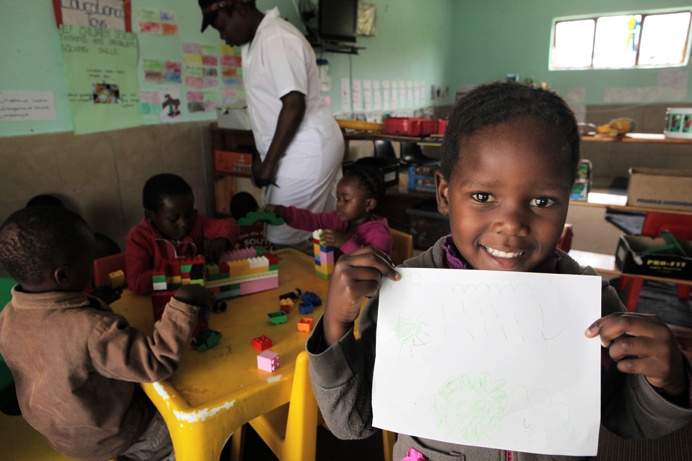 Mbalimba, 5, practices writing her name at the Save the Children Sizolomphakathi Early Childhood Development (ECD) Centre in Mpumalanga Province. Many children in the area live in single-parent households, either due to separated parents, a deceased parent or an absent father. Originally an ECD centre play bus until 2009, Save the Children reopened as a permanent structure ECD centre for young children in the area, in 2011.