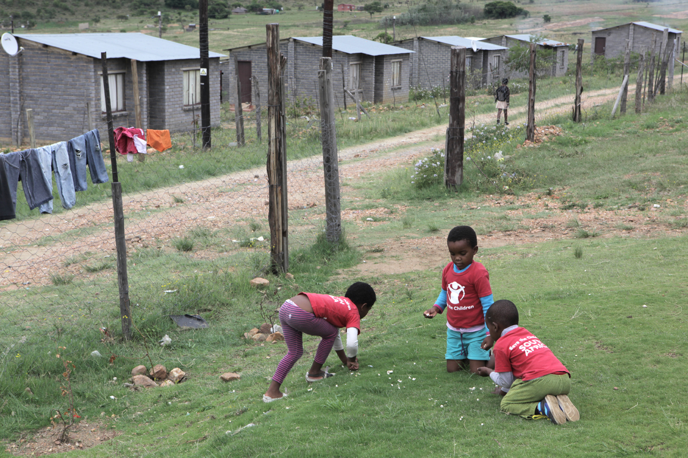 Children who attend the Save the Children Sizolomphakathi Early Childhood Development (ECD) Centre in Mpumalanga Province, play outside their home in the Thubulisha Reconstruction and Development Plan (RDP) community. Many children in the area live in single-parent households, either due to separated parents, a deceased parent or an absent father.