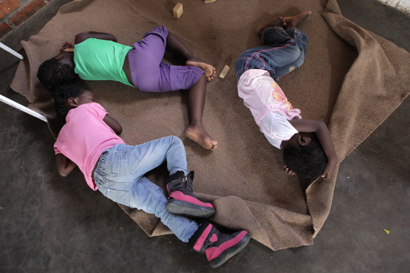Children nap on the floor at the Folovhodwe Creche in Mutale Municipality, Limpopo province. The Folovhodwe Creche is a basic facility currently operating out of the community church. Teacher Alice Tshisevhe is constructing a nearby building for the centre, and hopes to eventually become registered as a formal Early Childhood Development (ECD) centre. Save the Children has recently begun supporting a number of creches in the Musina area with learning materials, play structures and management support.