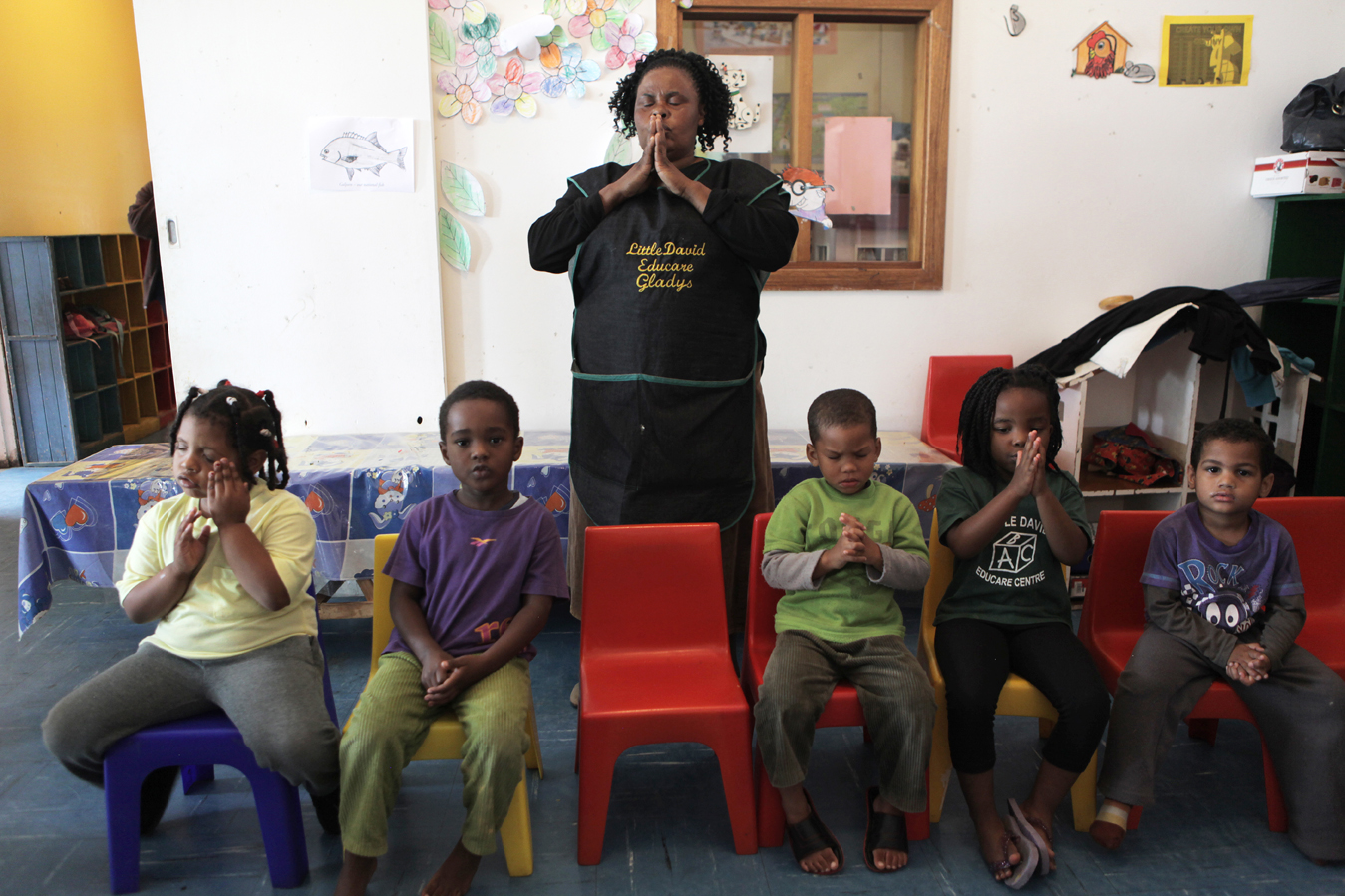 ECD teacher Gladys Hlatshwayo prays with the children before lunch at the Little David Educare Centre in Wentworth, a township on the southern side of Durban, in KwaZulu-Natal province. Over 92% of preschool children in KwaZulu-Natal attend unregistered ECD centres (crèches). Save the Children, operating in KZN for over 50 years, recognised the need to support crèches in the area with better management skills and access to learning materials, as well as running the crèche forums and supporting crèches with registration to become ECD centres.