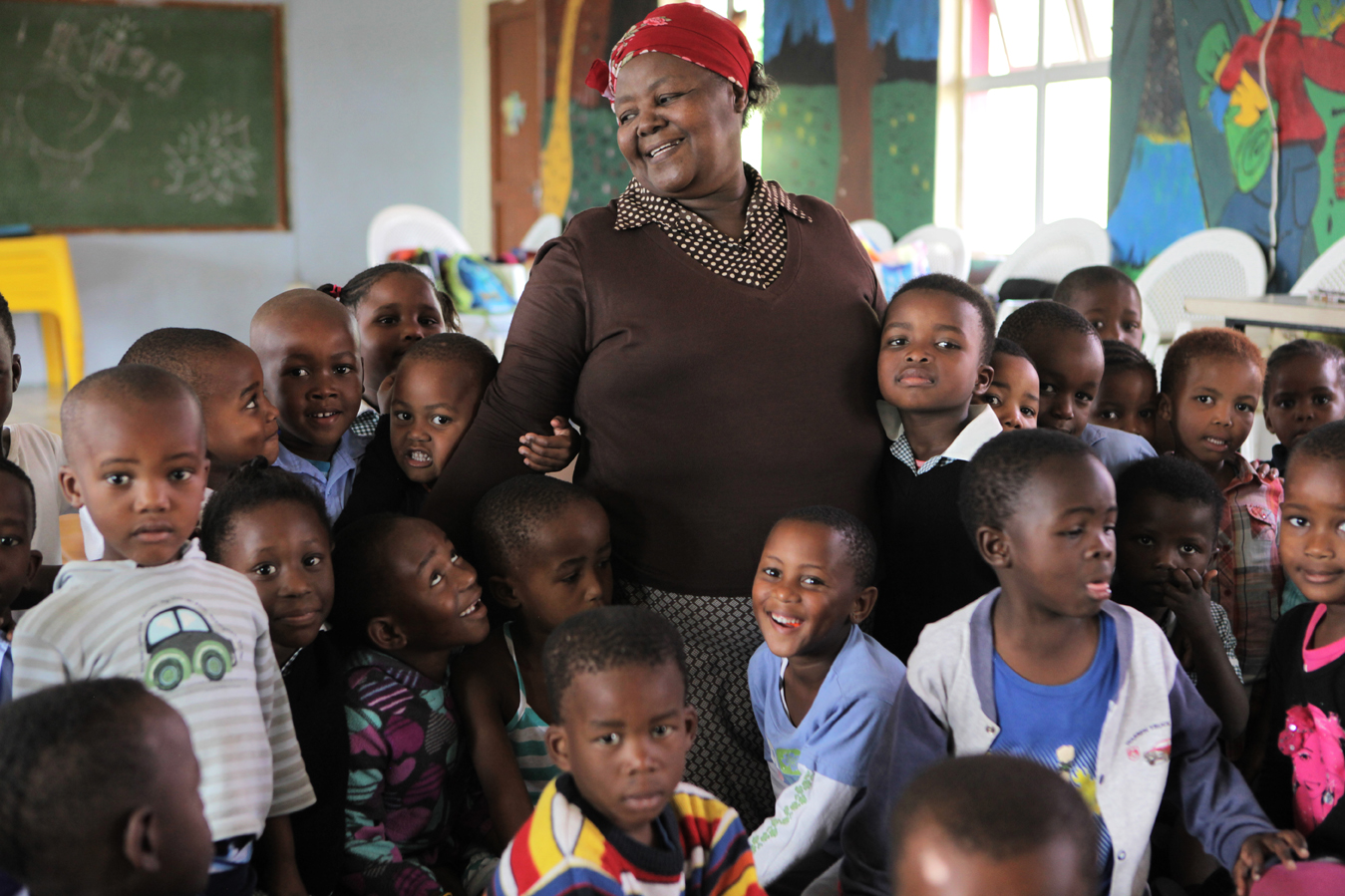 Principal Ethel Ngcobo, with her students at the Zamani ECD Centre on the outskirts of Durban in the eThekwini district. Ethel first opened as a crèche in 1995, responding to the need for children to be cared for while their parents were at work. After years of dedication and support from ABSA, the Outreach Foundation and Save the Children, she built a proper ECD centre. Over 92% of preschool children in KwaZulu-Natal attend unregistered ECD centres (crèches). Save the Children, operating in KZN for over 50 years, recognised the need to support crèches in the area with better management skills and access to learning materials, as well as running the crèche forums and supporting crèches with registration to become ECD centres.