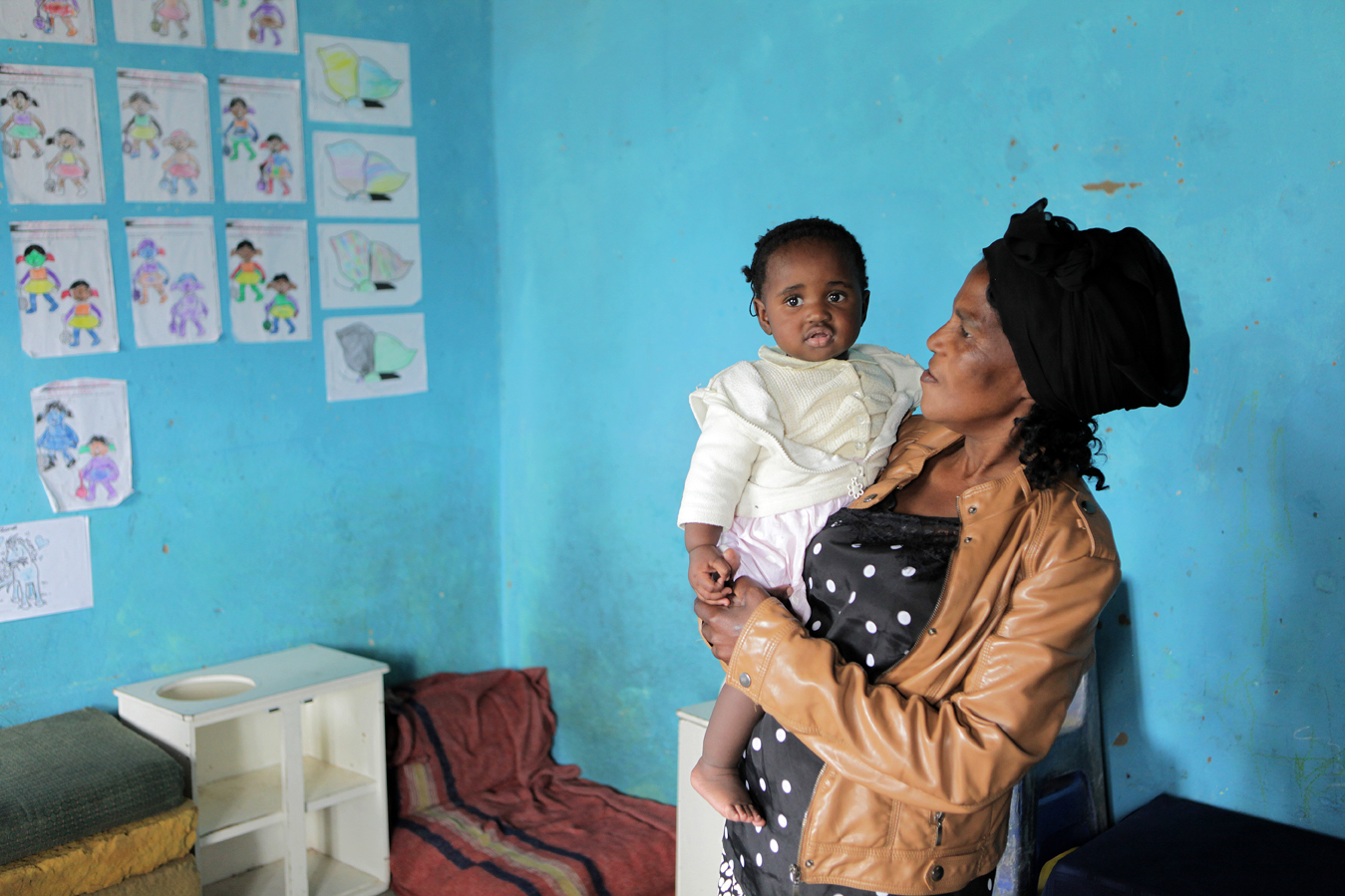 Faith Nkize, Director of the Siyazama Crèche in Hammarsdale, in the eThekwini district, with 9-month-old Snqobile. She first opened as a crèche in 1994, responding to the need for children to be cared for while their parents were at work. Faith is also a foster parent for six young children who have been orphaned by HIV/AIDS. She cares for these Orphaned and Vulnerable Children (OVC) as her own, responding to requests from caregivers and relatives to care for the children who were already attending her crèche. As South Africa's province with the highest HIV/AIDS prevalence, above 25%, Save the Children recognised the need to support caregivers to meet the physical, social and emotional needs of 200 orphaned and vulnerable children who are in 'informal' foster care.