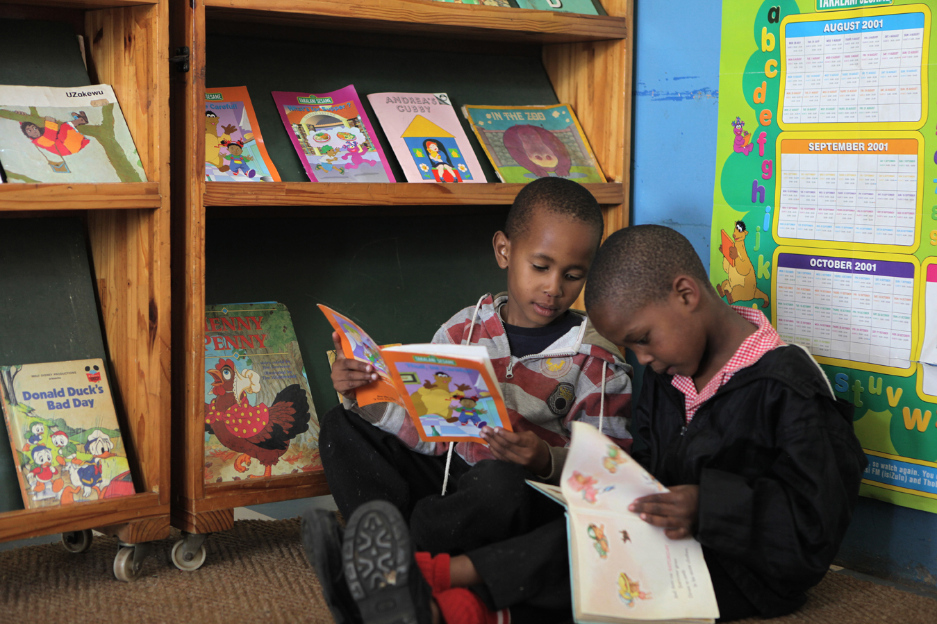 Nhlakanipho, 4, and Lubabalo, 4, read books at the Khulakahle David Beare ECD Centre on the outskirts of Durban in the eThekwini district. Principal Nokthula Zulu first opened as a crèche in 1987, responding to the need for children to be cared for while their parents were at work, and registered as a formal ECD centre in 1998. Over 92% of preschool children in KwaZulu-Natal attend unregistered ECD centres (crèches). Save the Children, operating in KZN for over 50 years, recognised the need to support crèches in the area with better management skills and access to learning materials, as well as running the crèche forums and supporting crèches with registration to become ECD centres.