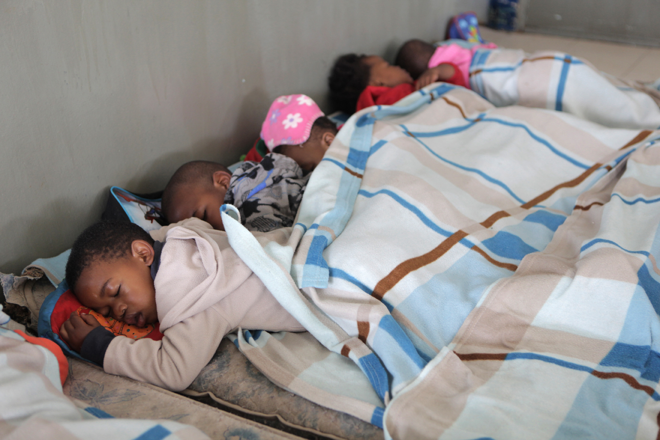 The youngest class take an afternoon nap at the Khulakahle David Beare ECD Centre on the outskirts of Durban in the eThekwini district. Principal Nokthula Zulu first opened as a crèche in 1987, responding to the need for children to be cared for while their parents were at work, and registered as a formal ECD centre in 1998. Over 92% of preschool children in KwaZulu-Natal attend unregistered ECD centres (crèches). Save the Children, operating in KZN for over 50 years, recognised the need to support crèches in the area with better management skills and access to learning materials, as well as running the crèche forums and supporting crèches with registration to become ECD centres.