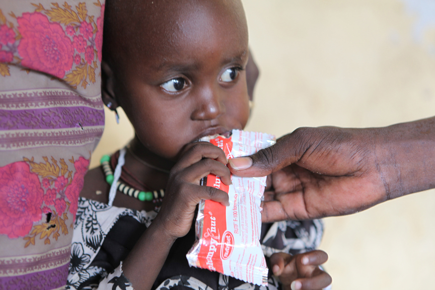 Mother Lokora Lokolong brings her daughter Lokoman, 2 years old, to the Save the Children Outpatient Therapeutic Programme for Plumpy Nut and Corn-Soy Blend (CSB) nutritional supplements, during a Child Health Day in Lomeyien Payam, Kapoeta North County, South Sudan.