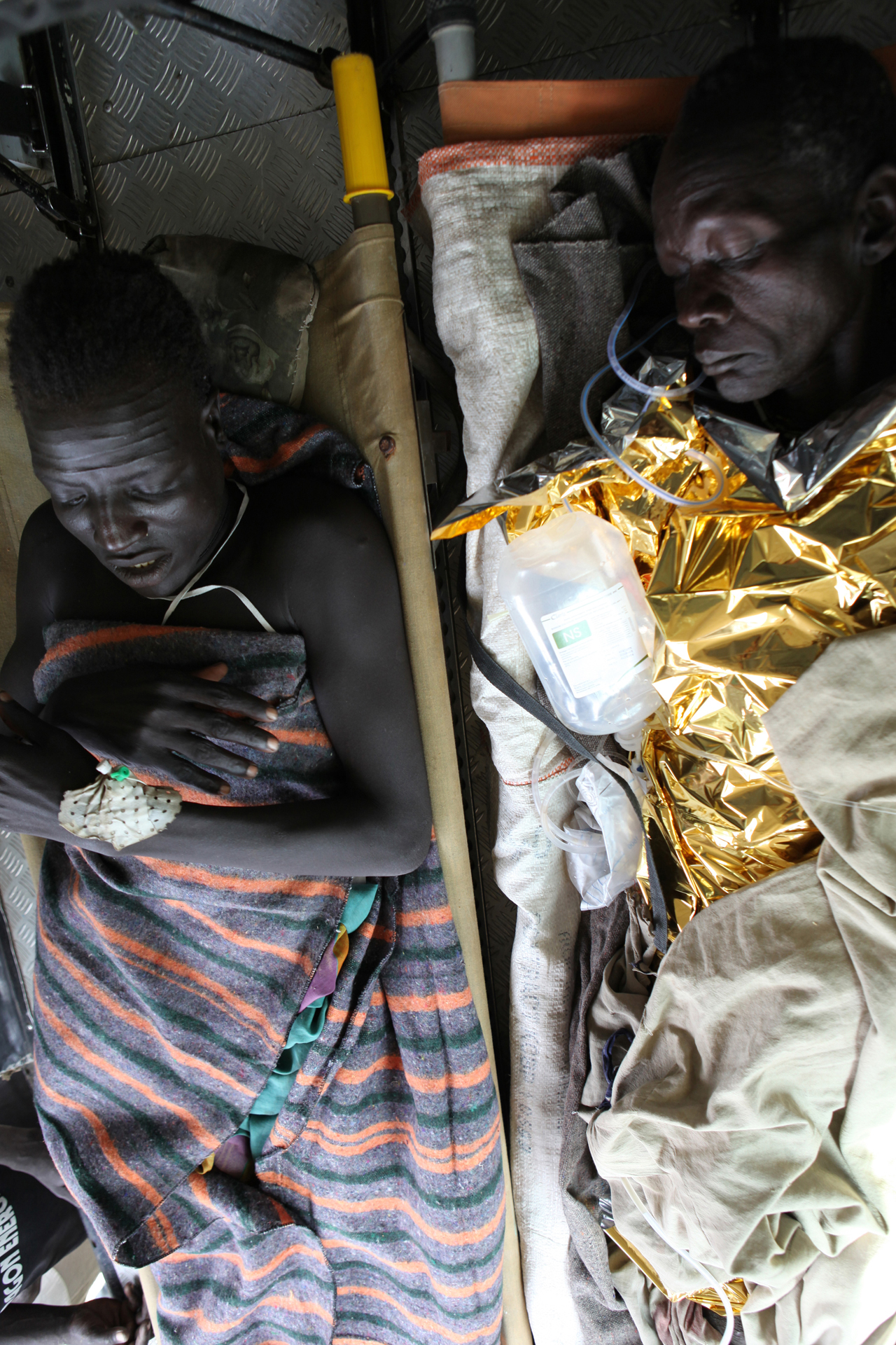 Patients are transported by air to the MSF-H Nasir Hospital in Upper Nile. Wiek Muon Mok, 52, (R) is flown from Pieri, Jonglei State, for surgery on a ruptured hernia and necrotic bowel extrusion due to traditional surgery three days prior. Rout Meet Makuach, 27, (L) suffered a gunshot wound and fractured leg in Lankien, Jonglei State, and also needs surgery.