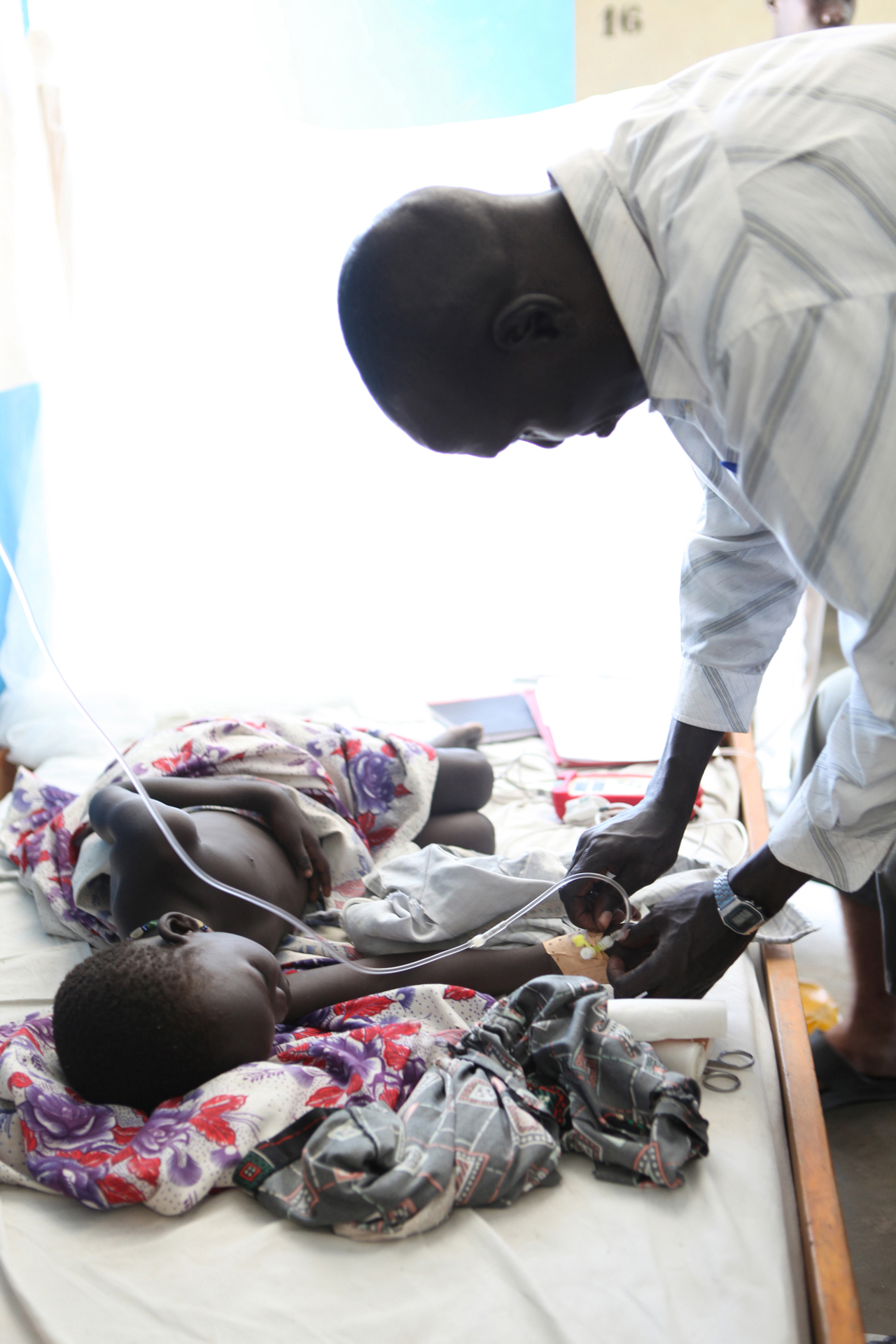 MSF Nurse Assistant James Mam Kongkong treats a girl suffering from cerebral malaria in the MSF Primary Health Care Center (PHCC) Pediatric Inpatient Ward in Pibor, Jonglei State. Pibor is one of the largest villages of the Murle people, who are an entirely nomadic community of cattle herders, and MSF is the only healthcare providing organisation operating in the area.
