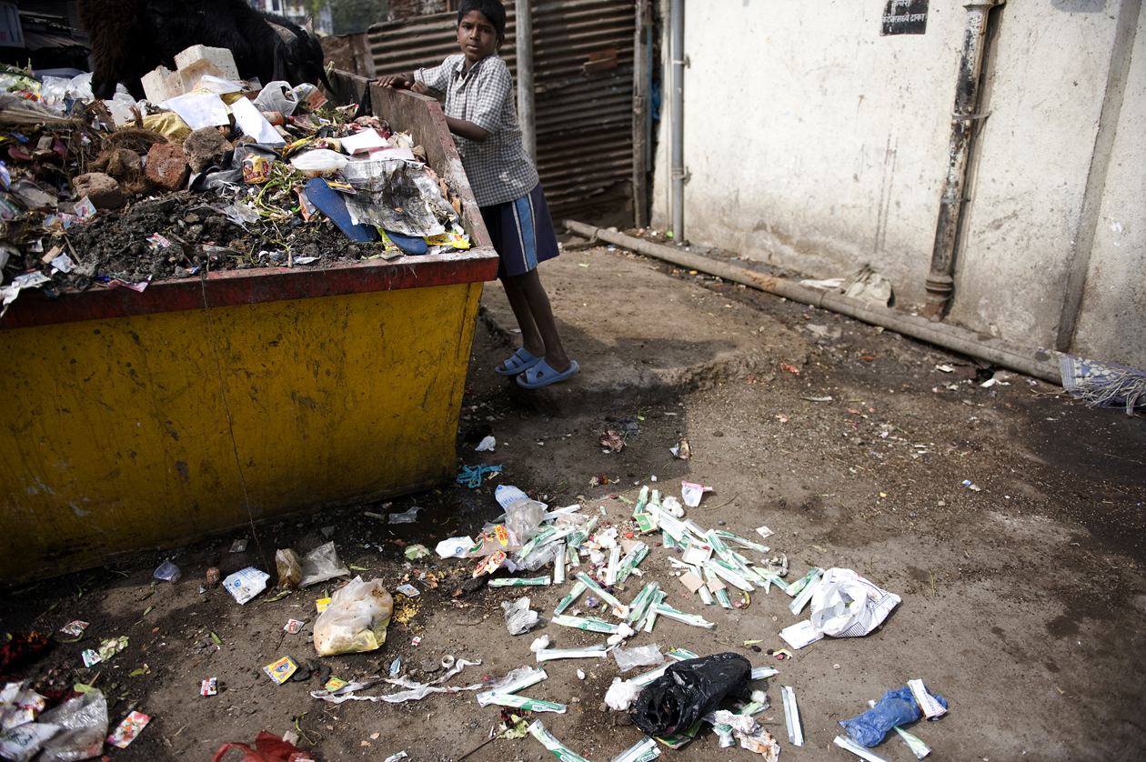 A child separates medical waste in a dumpster in Karvenagar Slum, Pune, India. The nearby clinic refuses to pay the city charges for proper waste disposal, and throws used syringes and other medical waste in the open dumpster.