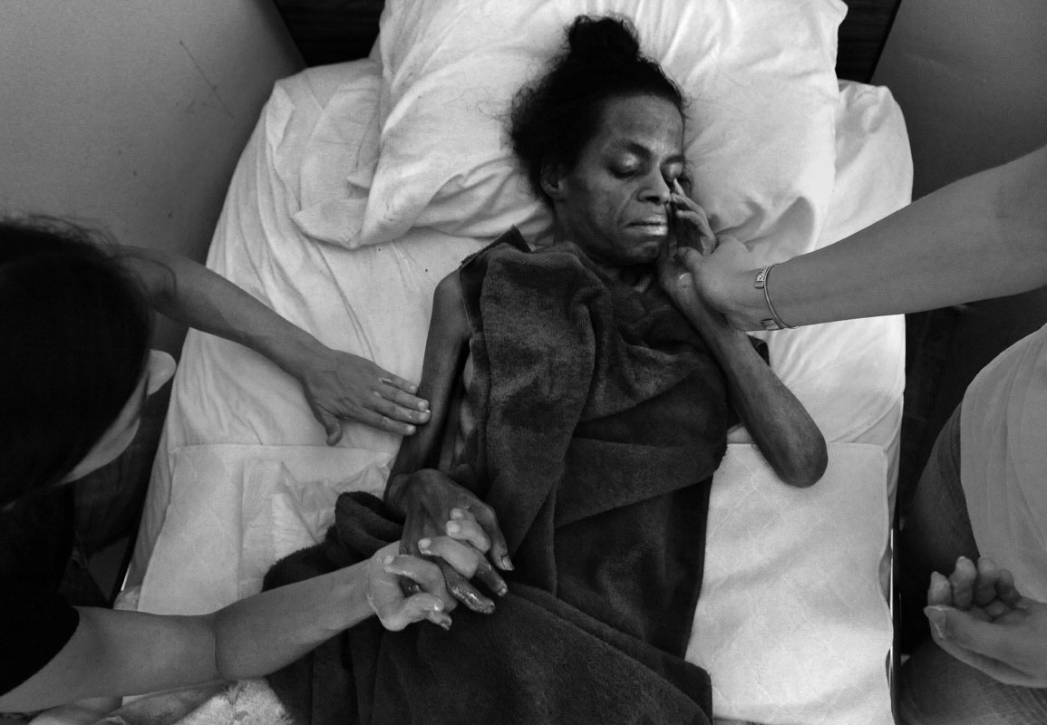 Eunice Minor's dry skin is kept moist by the caring and lotioned  hands of Angie Meyer, left, and Cameron Cochran, right.  Eunice Minor lies dying of A.I.D.S. at Joseph's House, an AIDS/cancer hospice.