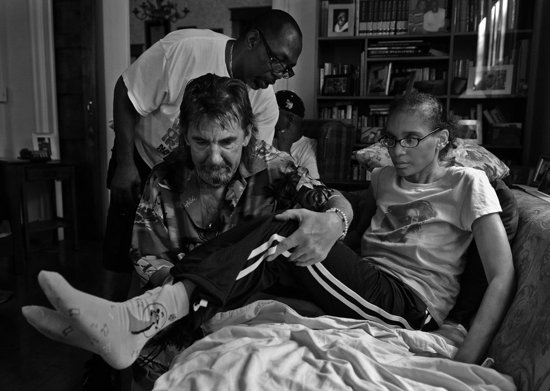 Lavada Vincent, a resident of Joseph's House who has died since this photo was taken, is helped to her seat by Pierre Langevin as Bobby Thames lends a hand at Joseph's House, an AIDS/cancer hospice.