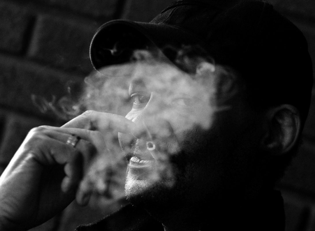 Despite having both throat cancer and AIDS, Michael Tyree smokes on the porch at Joseph's House, an AIDS hospice in Washington, DC.  In the past, Tyree was provided services by Miracle Hands, an HIV/AIDS provider in DC that is said to have fraudulently received millions of grant dollars, bypassing cash-strapped providers such as Josheph's House. Tyree has died since this photo was taken.
