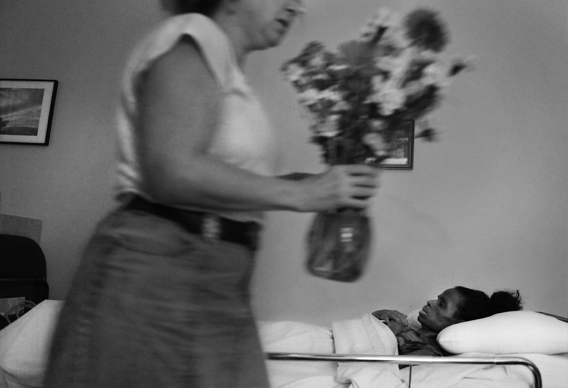 Patty Wudel, executive director, places flowers in the room of the body of Eunice Minor, who suffered from AIDS, at Joseph's House, an AIDS/cancer hospice in Washington, DC.  Wudel used some of the only clothes they had to dress Minor, who came to the house with little to nothing.  {quote}Often, the people who come here have been so sick for so long that by the time they get here, with all of that support, it's kind of an unconditional support of just love and just sticking by somebody who doesn't want to die and who does die,{quote} said Wudel. {quote}And so we stick by that person, not only with good end of life care and hospice care, just with gentle friendship and sometimes courage and sometimes just so much sadness. And our way is just to do that quietly, human being to human being within a caring community.{quote}