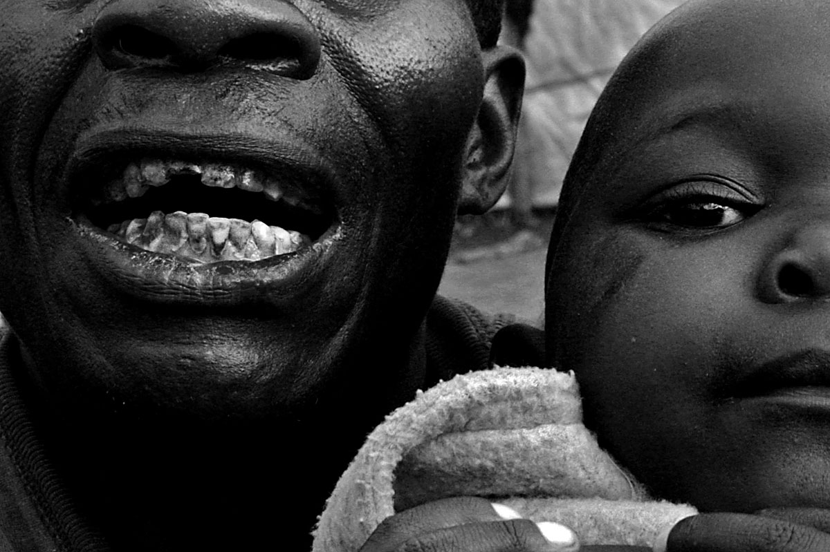 A man holds a child in a camp for internally displaced people in Shasha, DRC.  Because of violence, thousands of civilians have been displaced in the South Kivu region of eastern Congo, lending to the almost million people who have been displaced country-wide.