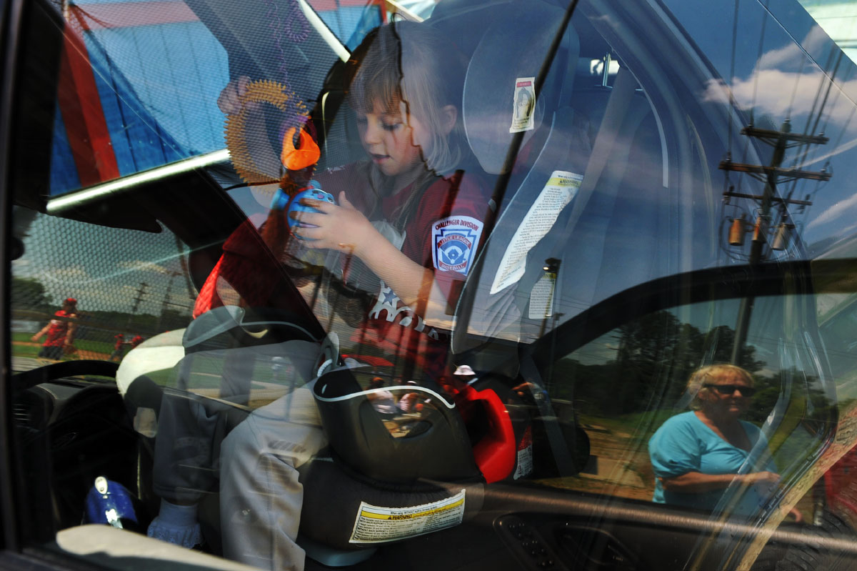 Gail Ertel, reflected in her car window,  at the baseball field where McKenzie plays on a Little League team for special-needs children.
