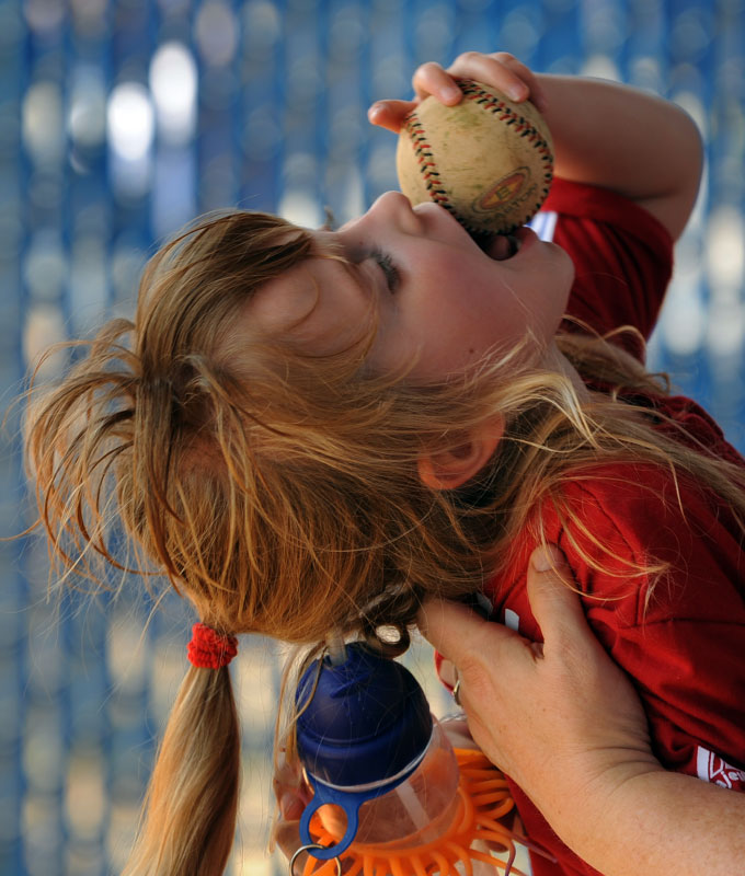 McKenzie Campbell, who is blind, autistic and has numerous other disabilities including limited senses of taste and smell, samples the texture of a baseball with her tongue during the child's baseball game in Woodbridge, VA.