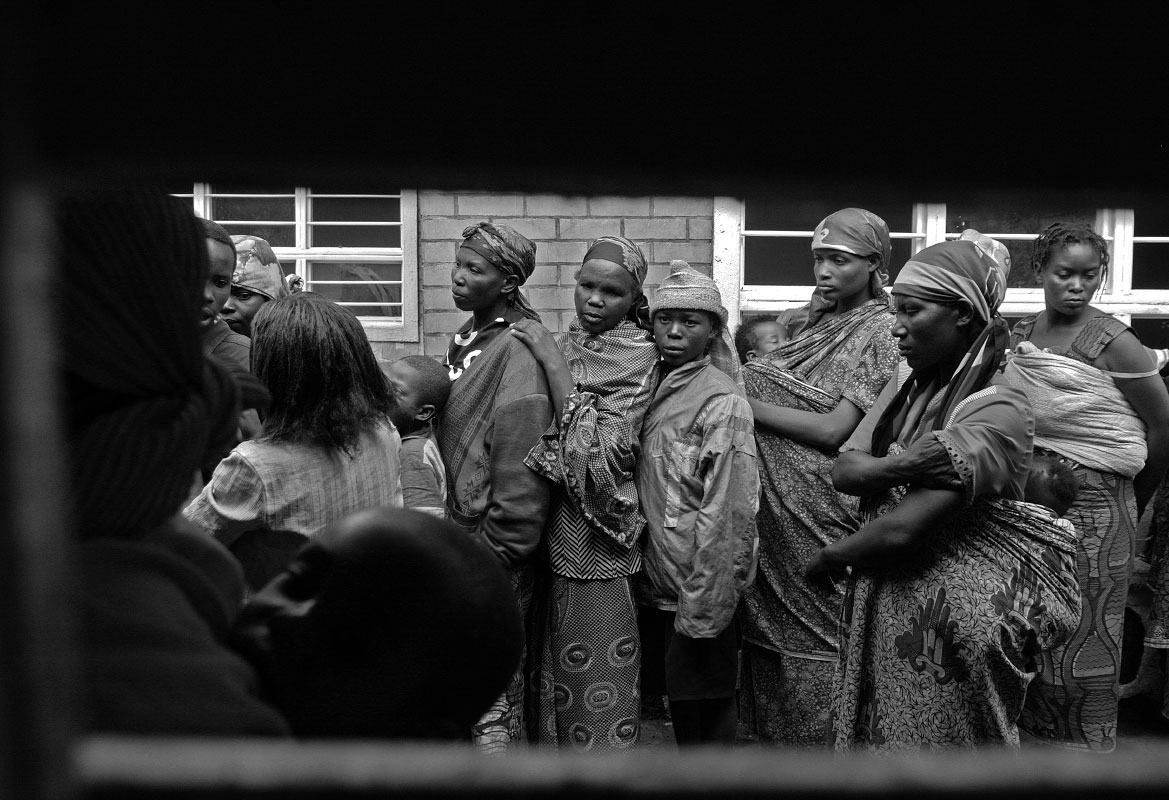 The families of Rwandan Hutu rebels stand in line for food at a transition camp of the UNHCR in Goma, Demcratic Republic of Congo.  Nervous about their transition from Congo back to Rwanda, many of these familes have not seen their home country in 15 years.
